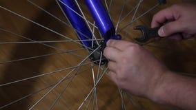 L'uomo prende la ruota fuori dalla bicicletta Sviti il dado dall'asse di ruota stock footage