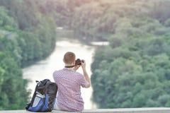 L'uomo prende le immagini da una collina Foresta e fiume qui sotto Fotografia Stock Libera da Diritti