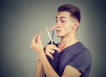 L'uomo preoccupato del bugiardo vuole tagliare il suo naso lungo Fotografia Stock Libera da Diritti
