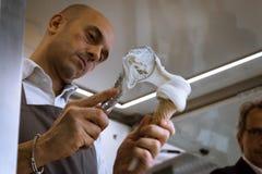 L'uomo prepara un cono gelato a Golosaria 2013 a Milano, Italia Immagine Stock