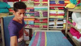 L'uomo produce il panno della stampa del bollo all'officina al nuovo mercato in Dacca, Bangladesh video d archivio