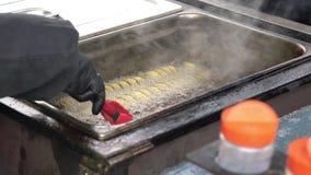 L'uomo produce la patata a spirale dorata fritta nel grasso bollente su un bastone di legno Croccanti torti, croccante portano vi archivi video