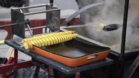 L'uomo produce la patata a spirale dorata fritta nel grasso bollente su un bastone di legno E archivi video