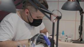 L'uomo professionale del manicure lucida e liscia le unghie della ragazza con un archivio di unghia archivi video