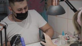 L'uomo professionale del manicure lucida e liscia le unghie della ragazza con un archivio di unghia stock footage