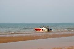 L'uomo prova a spingere la barca a bassa marea Fotografie Stock