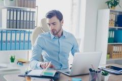 L'uomo qualificato giovani premurosi concentrato sta controllando la sua nota Immagini Stock Libere da Diritti