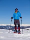 L'uomo in racchette da neve nelle montagne Immagine Stock