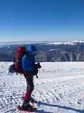 L'uomo in racchette da neve nelle montagne Fotografie Stock