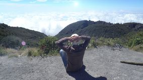 L'uomo raggiunge la cima della montagna Si siede e si rilassa, gode della vista dall'altezza sopra le nuvole Felice fiero della g video d archivio
