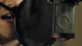 L'uomo registra la sua voce nello studio di registrazione stock footage