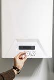 L'uomo regola il pannello di controllo della caldaia del riscaldamento di potere fotografia stock