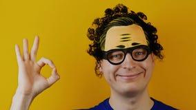 L'uomo riccio comico in modo divertente mostra quello tutto il okay video d archivio