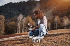L'uomo riccio con la barba che prepara lanciare il quadcopter immagini stock libere da diritti