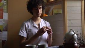 L'uomo riccio gode del tè di Puer a cerimonia di tè del cinese tradizionale Insieme di attrezzatura per tè bevente stock footage