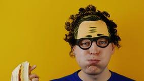 L'uomo riccio in modo divertente e comico con la bocca piena mastica un alimento archivi video