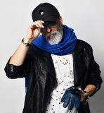 L'uomo ricco senior brutale in bomber e sciarpa blu lunga sta con i guanti in armi e tiene la visiera immagini stock