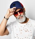L'uomo ricco senior brutale in maglietta del progettista tiene la visiera dei suoi uomini alla moda alla moda del berretto da bas fotografia stock libera da diritti