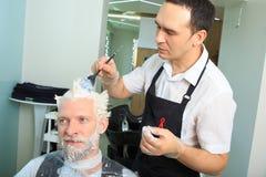 L'uomo ridipinge i capelli in un salone di bellezza immagini stock libere da diritti