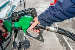 L'uomo riempie il carro armato di gas dell'automobile Il concetto dei cambiamenti di prezzi per i prodotti petroliferi e la benzi fotografia stock