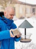 L'uomo riempie un alimentatore dell'uccello immagine stock