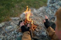L'uomo riscalda le mani vicino a fuoco di accampamento fotografie stock libere da diritti