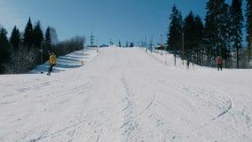 L'uomo in rivestimento giallo scende la montagna su un pendio dello snowboard accanto all'ascensore video d archivio
