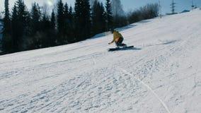 L'uomo in rivestimento giallo scende la montagna su un pendio dello snowboard accanto all'ascensore Vista laterale stock footage