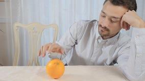 L'uomo rotola l'arancia sopra la tavola video d archivio