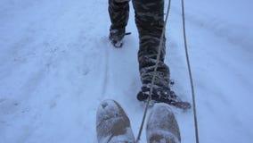 L'uomo rotola una ragazza su una slitta nella neve stock footage