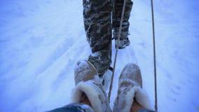 L'uomo rotola una ragazza su una slitta nella neve archivi video