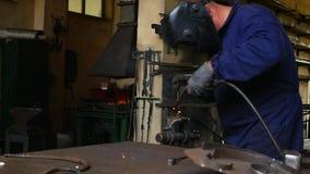 L'uomo salda il ferro in una maschera video d archivio