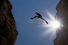 L'uomo salta attraverso Gap nella montagna Fotografia Stock Libera da Diritti