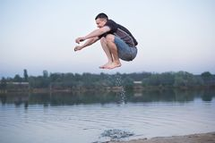 L'uomo salta sopra l'acqua del lago fotografia stock libera da diritti