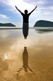 L'uomo salta sulla spiaggia Immagini Stock