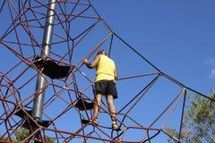 L'uomo scala alla cima di un telaio di scalata dei bambini Immagine Stock