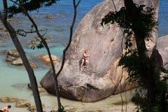 L'uomo scala su un ciottolo gigante sulla spiaggia Fotografie Stock Libere da Diritti