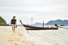 L'uomo scalzo con stoppia e lo zaino sta camminando sulla spiaggia di sabbia fotografie stock libere da diritti
