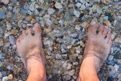 L'uomo scalzo ha affondato nell'acqua su Rocky Beach Fotografia Stock