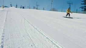 L'uomo scende la montagna su un pendio dello snowboard accanto all'ascensore stock footage
