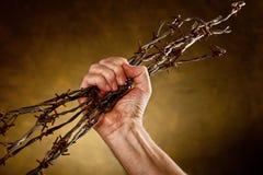 L'uomo schiaccia il filo spinato Immagini Stock Libere da Diritti