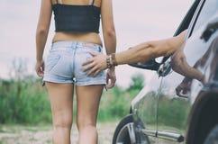 L'uomo schiaffeggia l'asino della ragazza Fotografie Stock