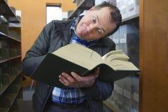 L'uomo sciocco legge un libro enorme delle biblioteche Fotografie Stock Libere da Diritti