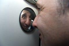 L'uomo sciocco osserva in specchio rotondo fotografia stock