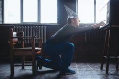 L'uomo sconosciuto in cappuccio della stagnola raggiunge fuori alla TV, UFO Immagini Stock