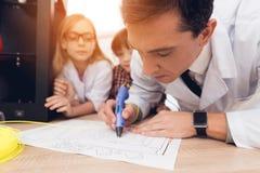 L'uomo scrive dalla penna 3d durante la lezione nella classe Fotografie Stock Libere da Diritti