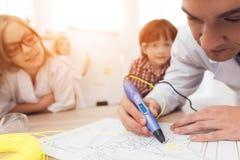 L'uomo scrive dalla penna 3d durante la lezione nella classe Immagini Stock Libere da Diritti