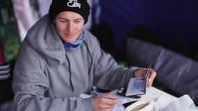 L'uomo scrive i partecipanti della lista nel concorso sulla stazione sciistica Dati del passaporto concorrenza stock footage