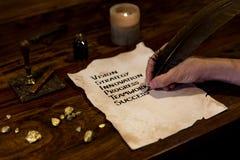 L'uomo scrive il mistero a successo su pergamena Fotografia Stock