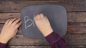 L'uomo scrive la parola BITCOIN con gesso su una lavagna, stilizzata come pensiero stock footage